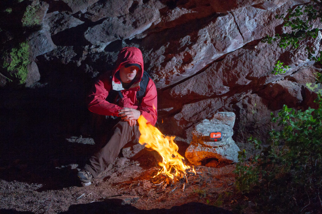 man sitting by survival fire with origin tool