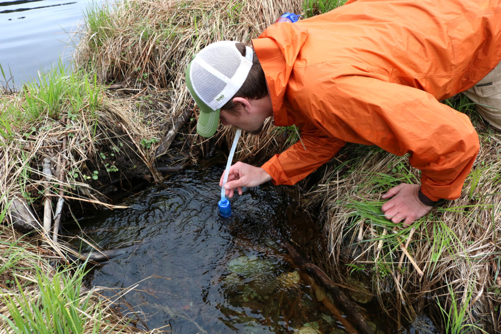 man drinking out of backcountry water source with rapidpure pioneer purifier straw