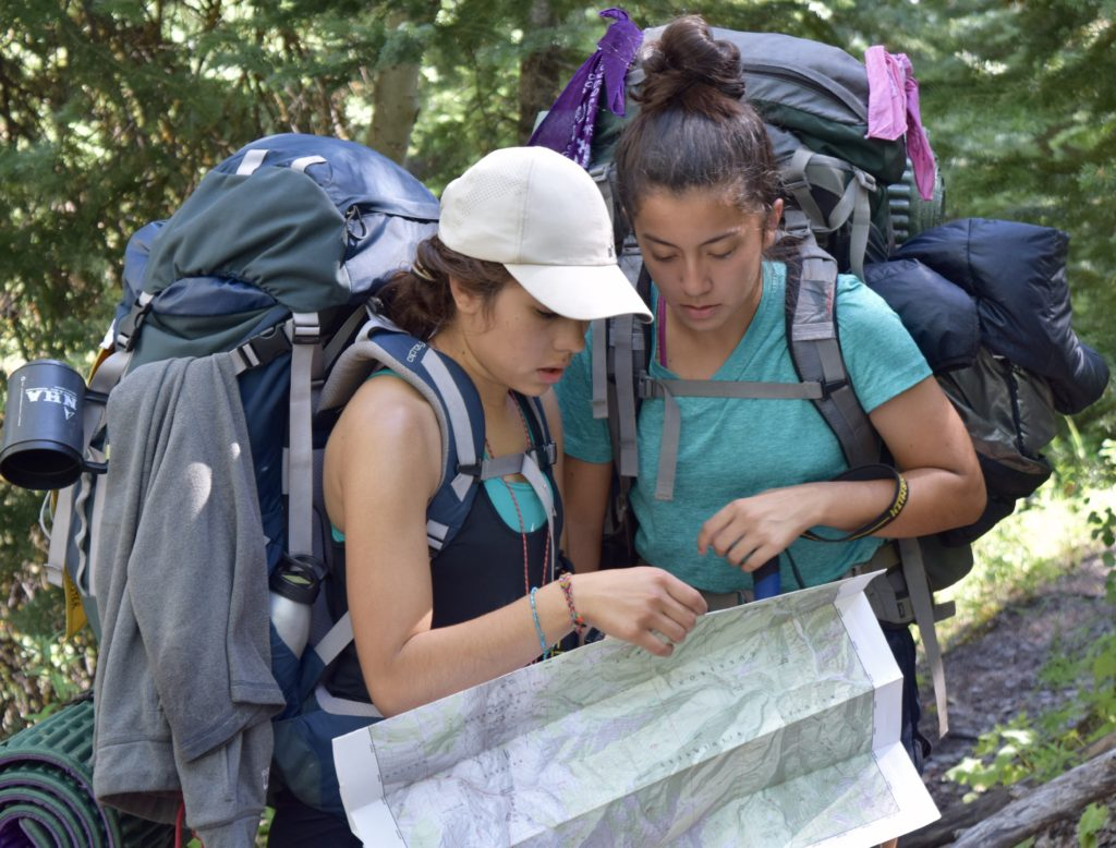 two girls looking at a map, one of the 10 essentials